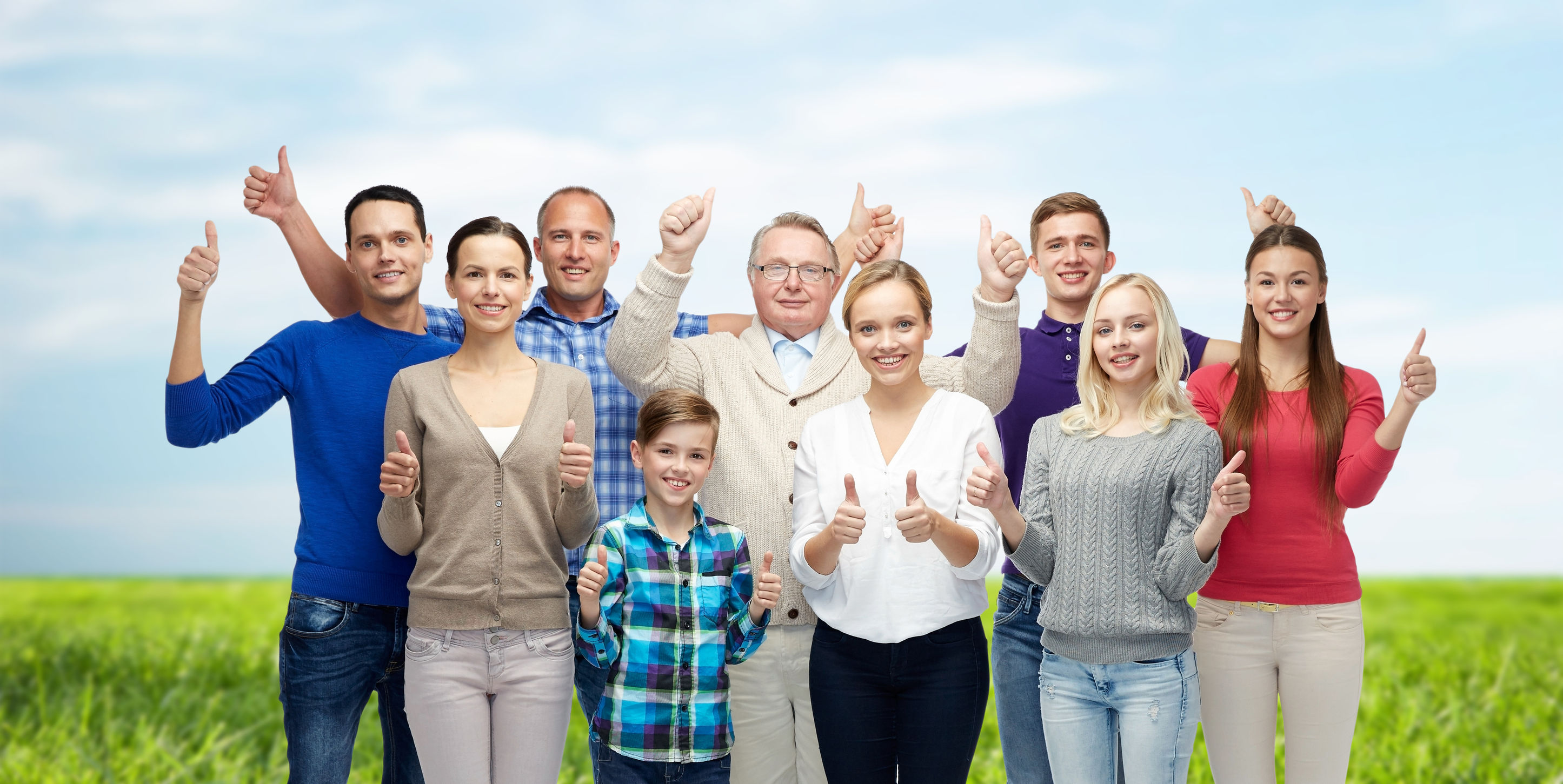 58800705 - gesture, family, generation and people concept - group of smiling men, women and boy showing thumbs up over blue sky and grass background