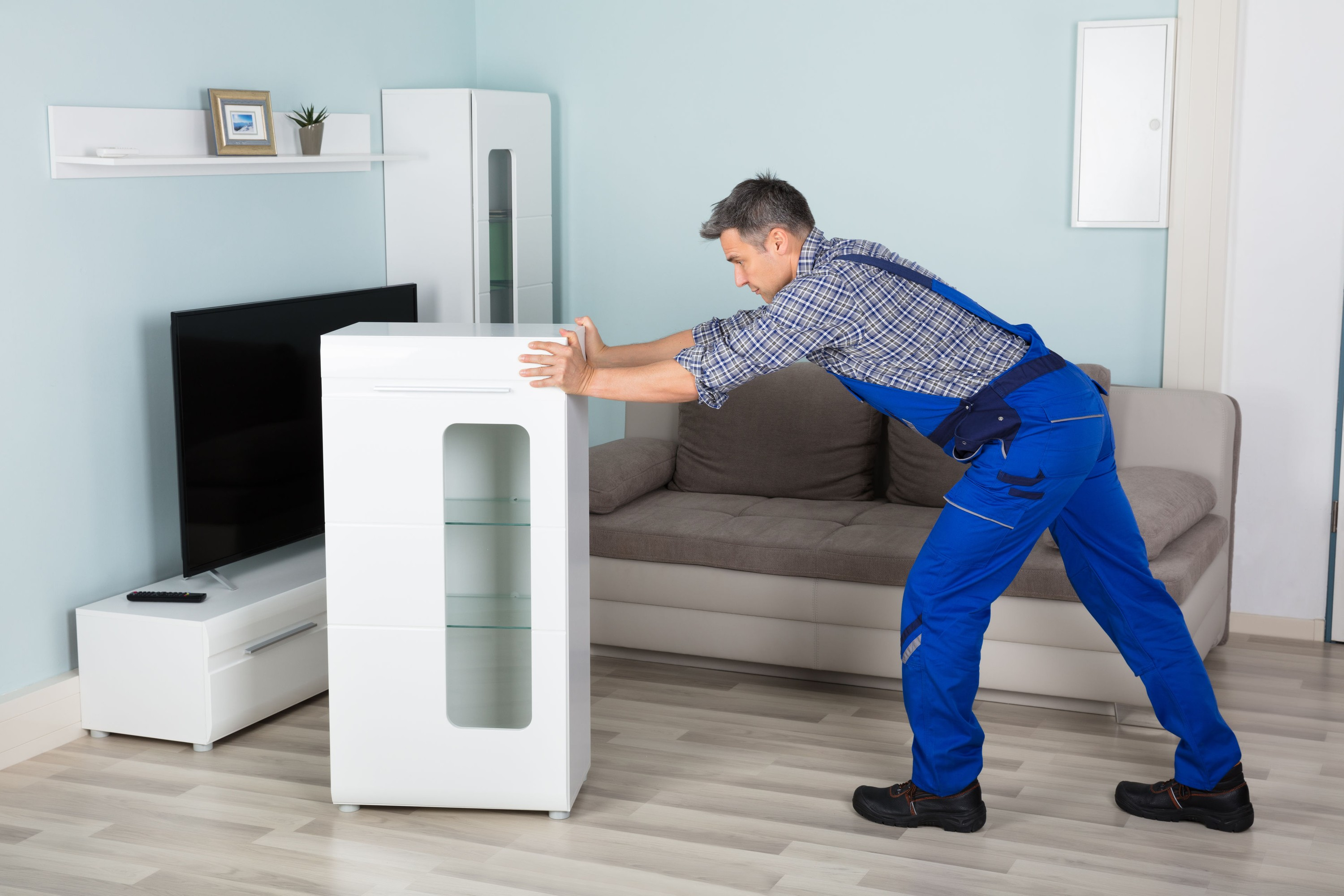 72006551 - mature male mover placing furniture in living room at home